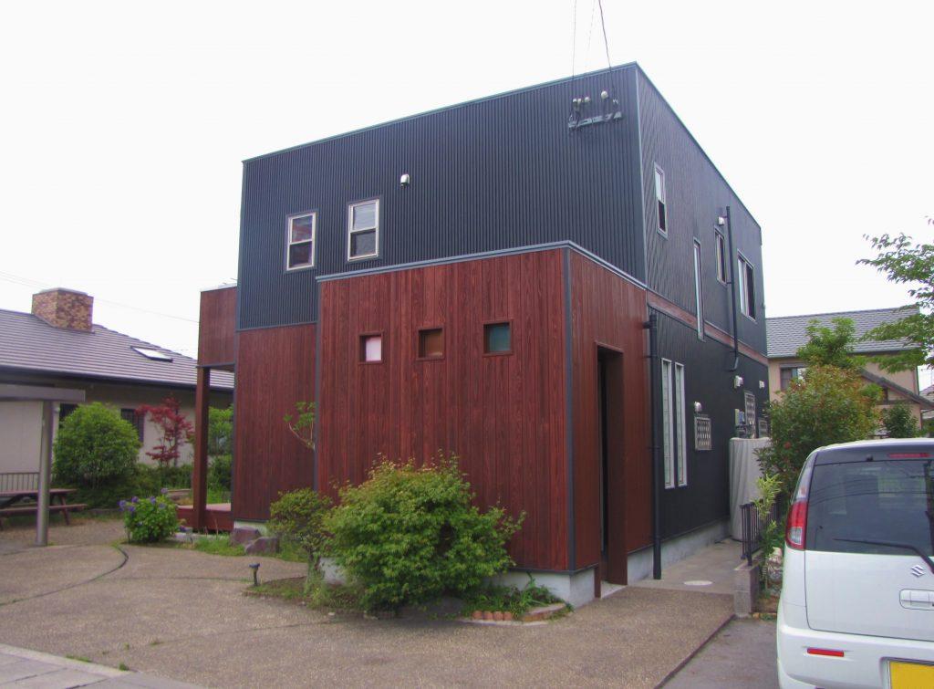 F様邸外壁屋根塗装工事後写真。1階玄関部分はアクセントとして木目を活かした赤茶色にし、アクセントが際立つよう他の壁は黒系で塗装しました。